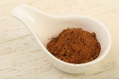 Cocoa powder. In the bowl over the wooden background royalty free stock image