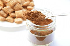 Cocoa powder. Spoon and cocoa pillows on the background Royalty Free Stock Photo