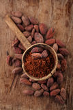 Cocoa powder in spoon on roasted cocoa chocolate beans backgroun Stock Image