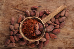 Cocoa powder in spoon on roasted cocoa chocolate beans backgroun Stock Images
