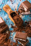 Cocoa in spoon and chocolate with creamy filling on blue board Royalty Free Stock Image