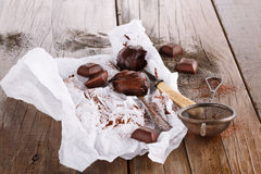 Cocoa spread on spoons and dark chocolate on wooden background. Cocoa spread on spoons, dark chocolate and cocoa powder on rustic wooden background. Selective stock photo