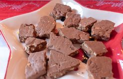 Cocoa Toffee on a plate. Selection of random sized pieces of delicious cocoa toffee served on a plate as Christmas sweet offering royalty free stock images
