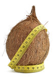 Cocoanut and a tape of measure. The concept of diet and health - coconut and measuring tape over white background stock photos