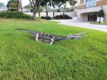 Cocodrilo artsy del metal que descansa en un césped de la hierba verde fotografía de archivo