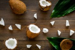 Coconut background. Whole and cut coconuts, pulp and palm leaves on dark wooden background top view Royalty Free Stock Images