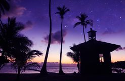 Coconut beach with a million stars and sunrise early morning.Asian man standing near the little hut. On the beach stock photography
