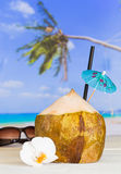 Coconut on the beach with straw and umbrella Stock Photo