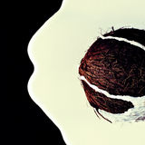 Coconut on black background with flowing down coconut milk Royalty Free Stock Photography