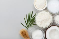 Coconut body scrub with ingredients on gray table top view. Homemade cosmetic for peeling and spa care. Flat lay. Stock Photo