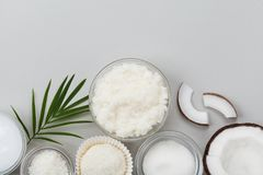 Coconut body scrub with sugar, oil and shavings on gray table top view. Homemade cosmetic for peeling and spa care. Flat lay. Coconut body scrub with sugar, oil Stock Photos