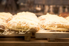 Coconut bread on wooden board at display bakery shop Stock Photos