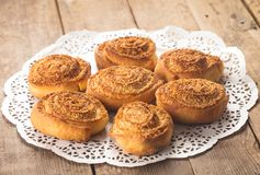 Coconut buns. Coconut rolled buns on the wooden table Royalty Free Stock Images