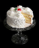 Coconut cake on a crystal cake stand Royalty Free Stock Image