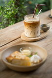 Coconut cake and ice coffee. On a wood table Stock Image