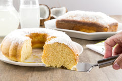Coconut cake with slice on the table Stock Image