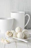 Coconut candies pile in white plate and cups Royalty Free Stock Photos