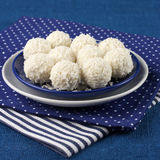 Coconut candies. In plate on blue napkins stock images