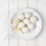 Coconut candies on white wood Stock Photos