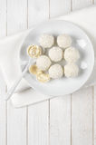 Coconut candies on white wood Stock Photo