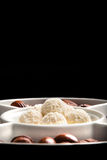 Coconut chocolate balls on plate isolated on black Stock Photo