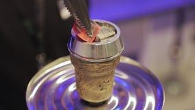 Man preparing hookah bowl and coald for smoking shisha. Hot embers for a hookah. Coconut Coals on Aluminum foil on stock video