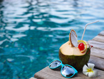 Coconut cocktail with drinking straw by the swimming pool Royalty Free Stock Image