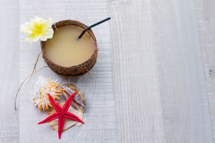 Coconut cocktail, starfish and shells on the deck Royalty Free Stock Images