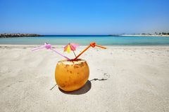 Coconut cocktail with straw and colorful umbrella on a beach. Coconut cocktail with colorful umbrella and two straws on a beach, summer holiday concept Royalty Free Stock Photography