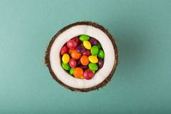 Coconut with colorful candies. royalty free stock image