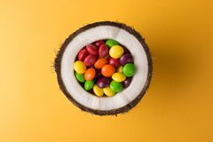 Coconut with colorful candies. royalty free stock photos