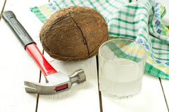 Coconut with crack, coconut water, hammer and napkin Stock Photo