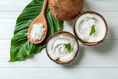 Coconut cream in nuts. On wooden background royalty free stock photo