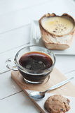 The Coconut Creme Brulee is sugary flavours and drink with hot americano black coffee on white wooden table background Stock Image