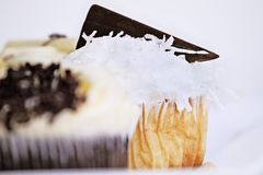 Coconut Cupcake with Chocolate Wedge. Pretty coconut frosted cupcake decorated with a wedge of dark chocolate. Extreme shallow depth of field with selective stock photos