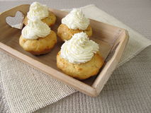 Coconut cupcakes with whipped cream on tray Stock Photos