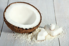 Coconut. Cut coconut with coconut flakes on white wood background Stock Photos