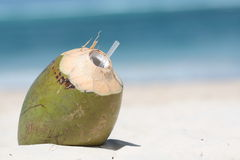 Coconut drink. On the sand with sea in background Royalty Free Stock Photo