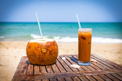Coconut drink and ice coffee on the wooden table Stock Images