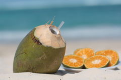 Coconut drink and oranges. On the sand with sea in background Stock Photos