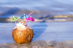 Coconut with drinking straw, umbrellas and flowers Royalty Free Stock Images