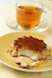 Coconut flan. On a yellow plate and a cup of tea Royalty Free Stock Photo