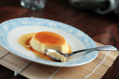 Coconut Flan close-up. Coconut flan dessert on a wooden dinner table Royalty Free Stock Photo