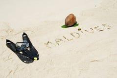 Coconut fruit and snorkeling. Maldives written in a sandy beach with coconut and snorkeling equipment Stock Photo