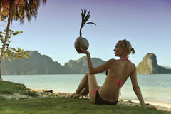 Coconut. Girl hold coconut sittig on the beach Stock Images