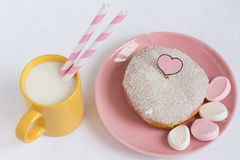 Coconut Glazed Donut with Marshmallows and Milk. Coconut Glazed Donut with Marshmallows and a Cup of Milk with Two Paper Straws Stock Photo
