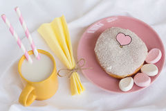 Coconut Glazed Donut with Marshmallows and Milk. Coconut Glazed Donut with Marshmallows, a Paper Napkin with a Twine Bow and a Cup of Milk with Two Paper Straws Royalty Free Stock Image