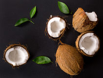 Coconut with green leaves  on a black Royalty Free Stock Photo