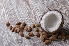 Half coconut and almonds on a wooden stand royalty free stock image