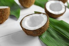 Coconut half with green leaf. On wooden background Royalty Free Stock Images